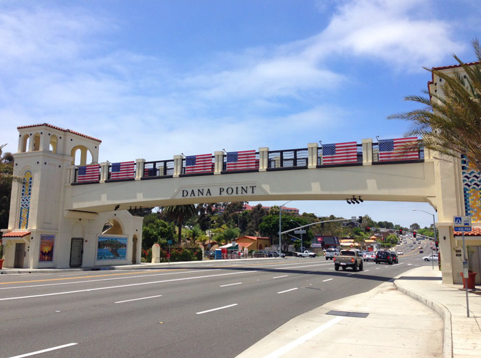 Image of the Dana Point Bridge with American Flags hanging down celebrating the 4th of July Independence Day